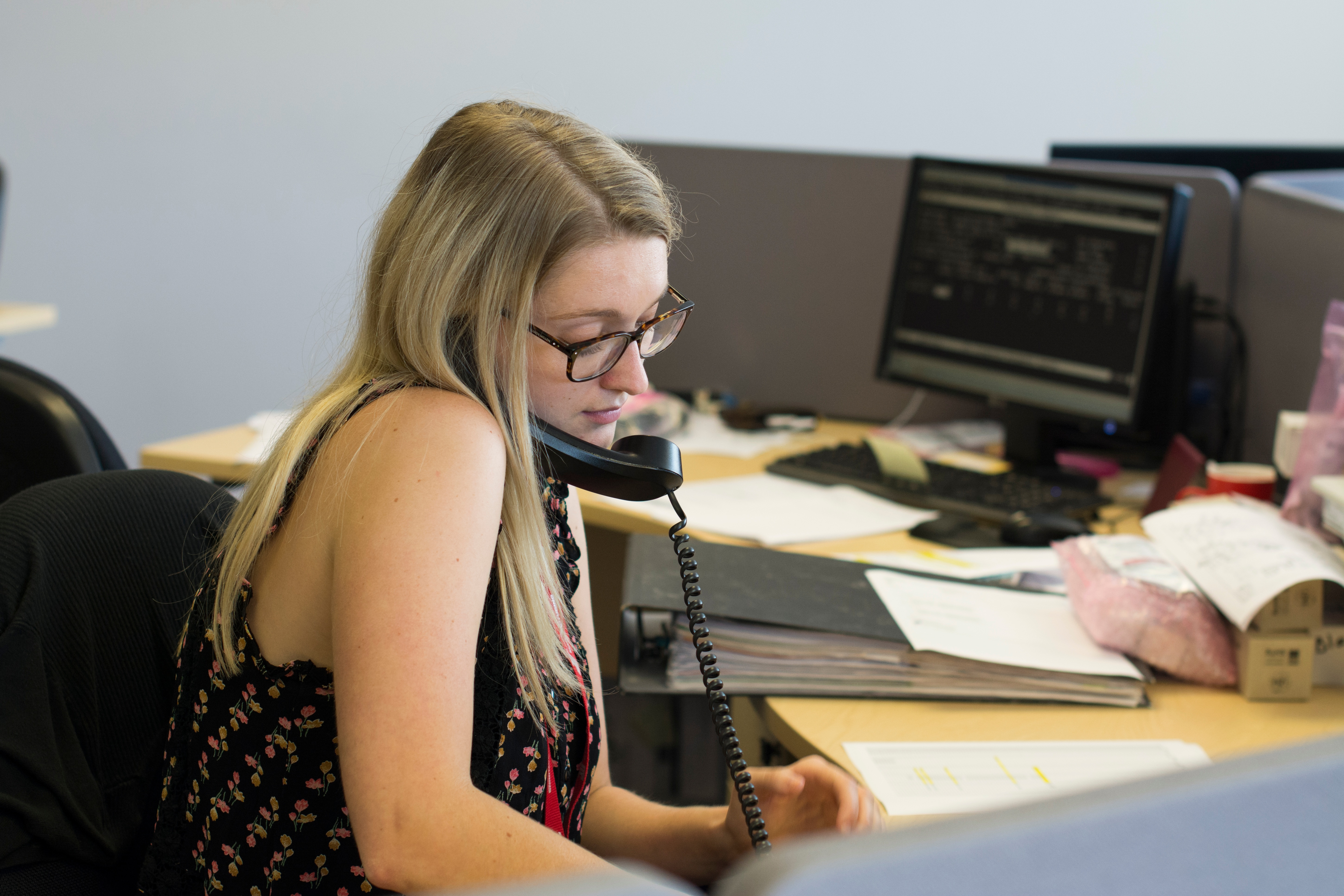 A commercial graduate sitting at her desk on the phone to a customer