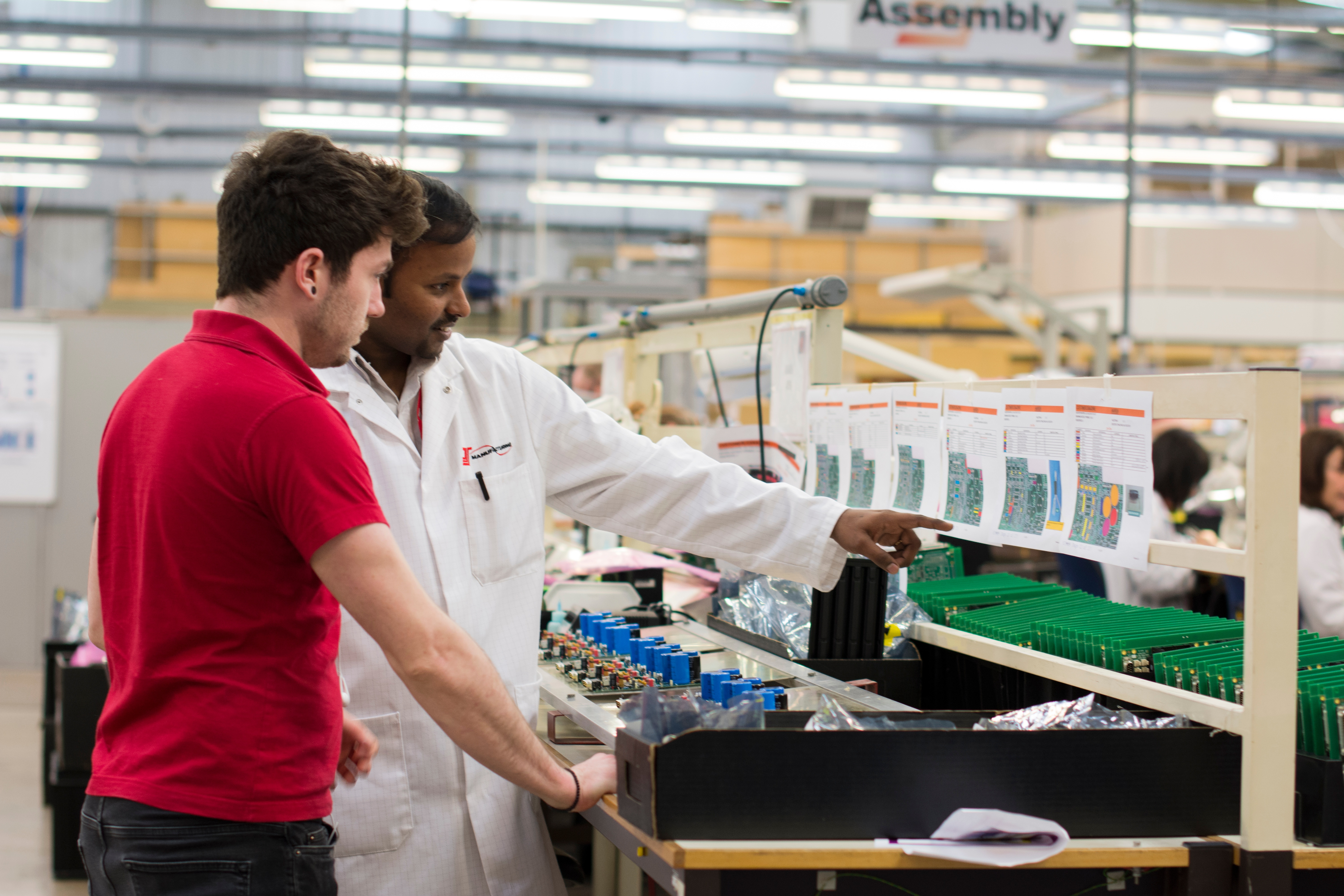 An engineer showing an engineering placement student a set of customer drawings by pointing to them